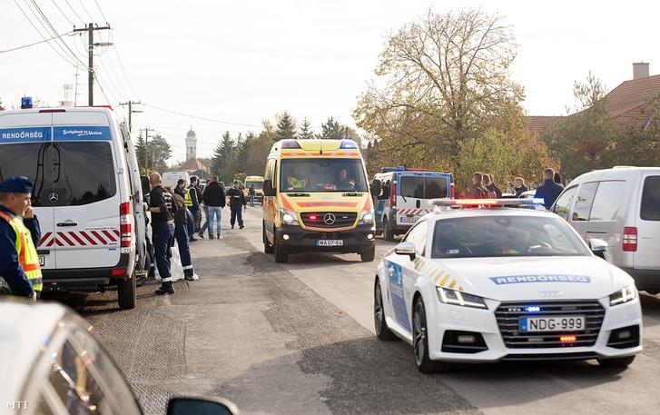 A 74 éves sérült elkövetőt viszi el egy mentőautó rendőri kísérettel 2016. október 26-án Bőny főutcáján.