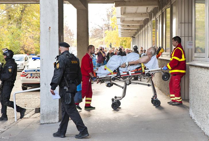 Mentősök tolják ki a győri kórházból a bőnyi rendőrgyilkosság gyanúsítottját, hogy átszállítsák a tököli rabkórházba.