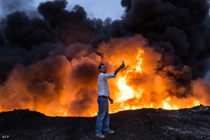 A lájk az Irakban is lájk: egy iraki civil lő egy szelfit a lángokkal.