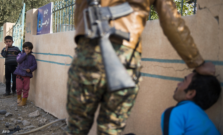 Egy harcok elől menekülő férfit kérdeznek ki iraki katonák Moszul külvárosában.