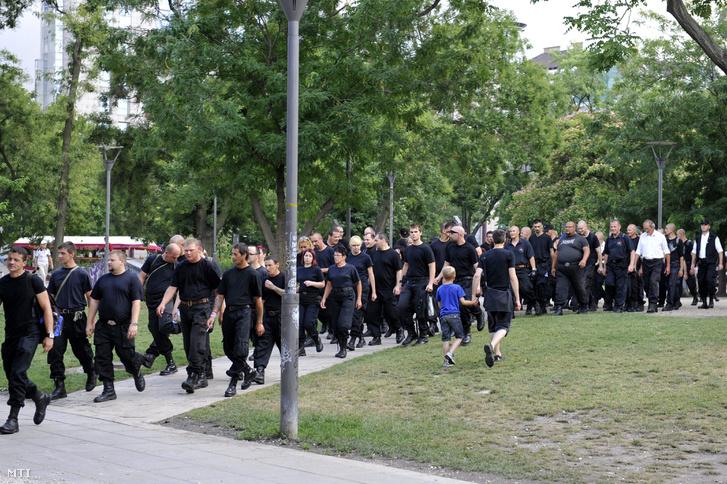 Az Új Magyar Gárda Bajtársiasság napján tartott megemlékezésének sötét ruhába átöltözött résztvevői a 18. Budapest Pride a leszbikus meleg biszexuális transznemű és queer (LMBTQ) közösség fesztiválja felvonulásának útvonalához vonulnak az Erzsébet téren 2013. július 6-án.