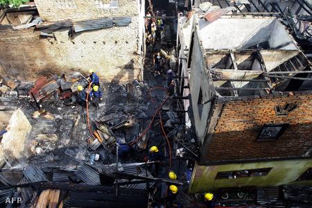 Tűzoltók vizsgálnak egy földrengés következtében kiütött tűz miatt leégett házat Szumátrán.