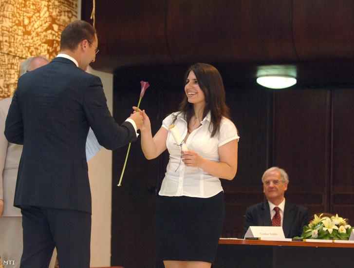 Tombor András az intézmény elnöke virággal köszönti az egyik végzőst a Mathias Corvinus Collegium 2008/2009. tanévzáró egyben diplomaosztó ünnepségén, 2009. június 19-én. Jobbra Sólyom László volt köztársasági elnök.