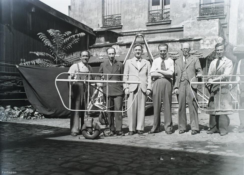Balról a harmadik öltönyös férfi Asboth, a másik három jól öltözött, öltönyös férfi valószínűleg befektetők, együtt pózolnak a fékész vázszerkezet előtt.