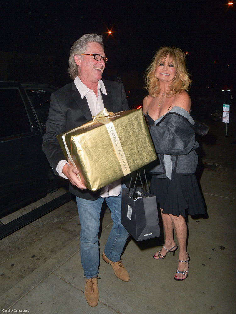 Természetesen nem egyedül, hanem Kurt Russellel ment bulizni, aki egy hatalmas ajándékcsomagot is cipelt.