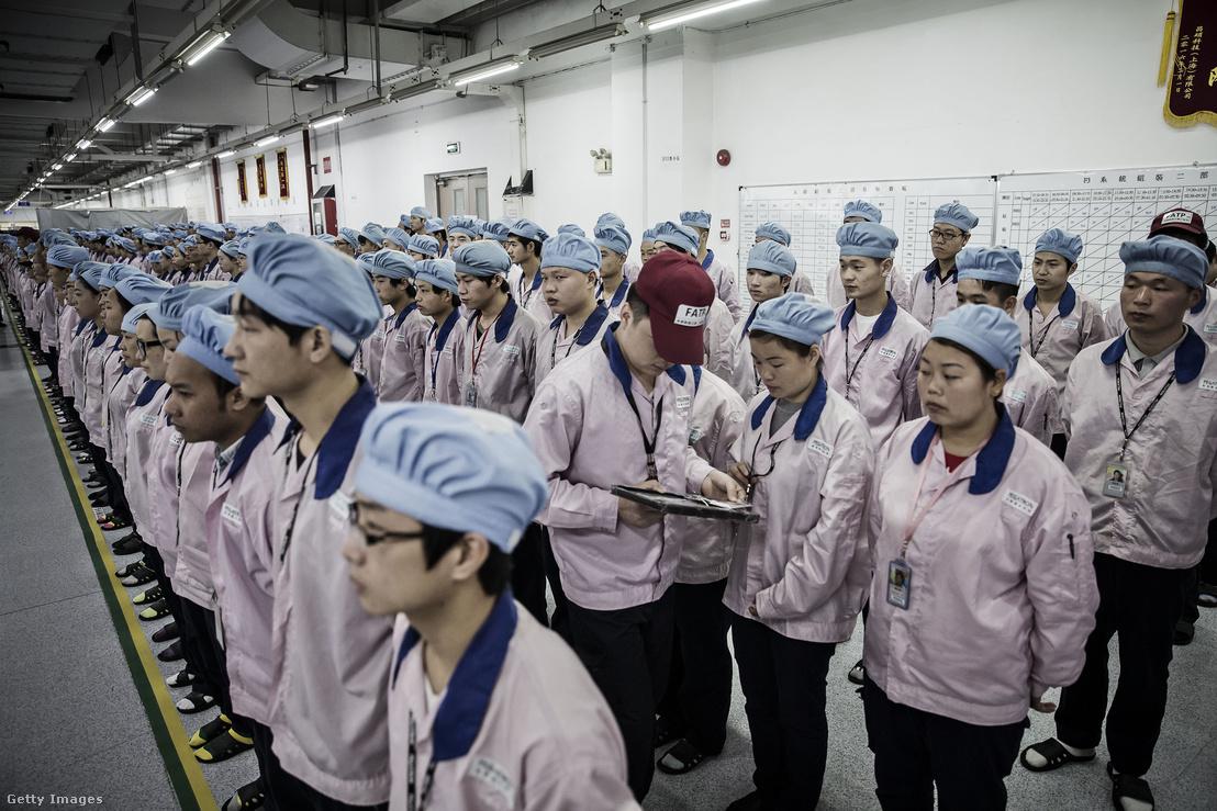 Ipadről ellenőrzi egy munkavezető a dolgozók kártyáit egy műszak előtt az Apple egyik kínai partnerének gyárában.