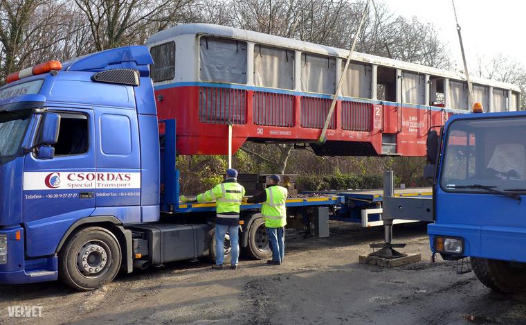 Az egyenként tíz tonna súlyú és 16 méter hosszú kocsikat egy nagy méretű daru emelte át a különleges szállítójárművekre