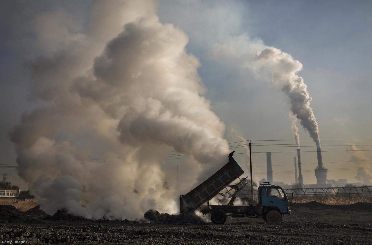 A teherautó éppen hulladékszenet pakol le a gyárak és füstjük árnyékában. A légszennyezés elleni harc fő ellensége a szén, amely a kínai energiatermelés közel kétharmadát adja, és az iparban is rengeteget használnak fel belőle. A baj csak az, hogy az alternatívák költségesek, a szénnel való radikális szakítás esetén pedig rengetegen elvesztenék a munkahelyüket. Politikailag tehát nem könnyű keresztülvinni a változásokat, helyi szinten (a korrupció mellett) ezért is problémás a pekingi ukáz követése.