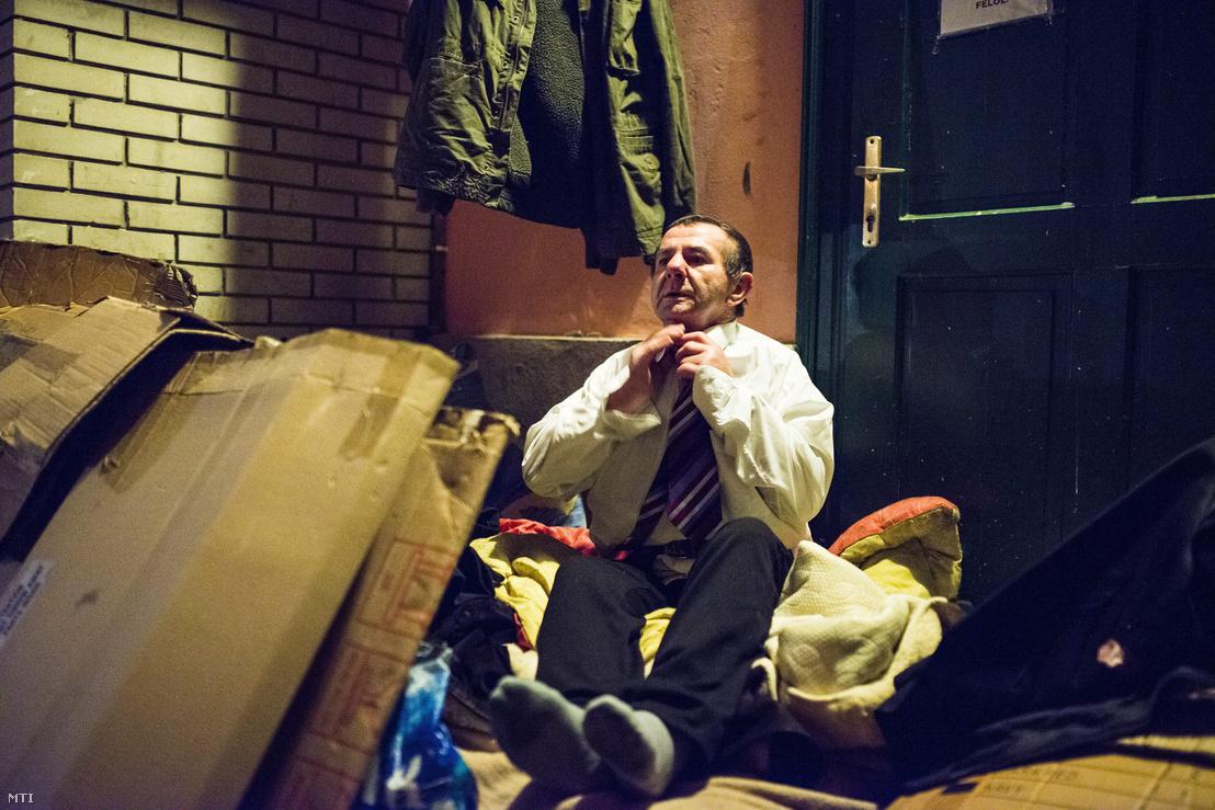 Az éjféli szentmisén résztvevő Antal Barnabás József hajléktalan leveszi elegáns ruháját az alvóhelyén Nyíregyháza belvárosában 2014. december 24-én.