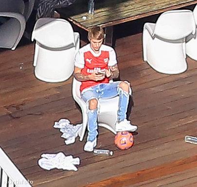 Ücsörög a kupi kellős közepén, egy focilabdát piszkál, és közben a mobilját nyomkodja