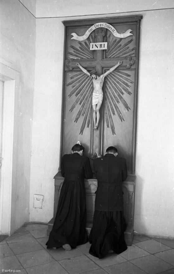 """Ismeretlen helyen készült fotó, papok a feszület előtt az ötvenes években. Ez már az állam és egyház közötti szerződés utáni """"csontváz,"""" a templomok és a szigorúan azok falai között lelkészkedő papság. Pedig ahogy az egyik """"békepap"""" 1953-ban summázta: """"ami nélkülünk történik, az ellenünk szokott történni."""""""