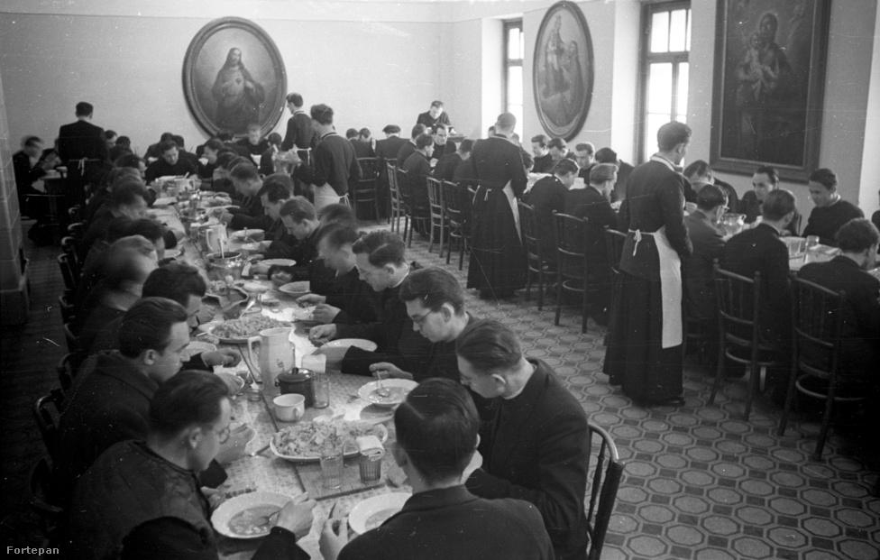 """Esztergom, az egyházmegyei szeminárium ebédlője az ötvenes évek végén. Aki a Népköztársaság kenyerét eszi, annak úgy is kell prédikálnia? Az 1949-es alkotmányra először a református és az evangélikus püspökök tettek esküt 1950 januárjában. 1951-ben, Grősz József kalocsai érsek letartóztatása után a katolikus püspöki kar sem látta értelmét a további ellenállásnak: felesküdtek és erre szólítottak fel minden papot is. A börtönből kiszabadult Grősz József kalocsai érsek így nyilatkozott a szemináriumi nevelésről 1956 júniusában: """"A szemináriumi nevelés és a teológiai oktatás normális mederben folyik, az egyházi törvények előírásai szerint, amint erről a budapesti és a szegedi szemináriumokban tett látogatásaim során meggyőződtem. Papnövendékeink egyházias szellemben, az egyházhoz és annak fejéhez való hűségben és a magyar haza, népünk szeretetében nevelődnek. Számuk megközelíti az ötszázat, ami az adott körülmények között szükségleteinknek megfelel. A múltban szemináriumainkkal kapcsolatban is voltak nehézségeink, remélhetőleg ezek is elsimulnak. Úgy érzem, az eddigi kibontakozás a normalizálódás felé halad."""""""