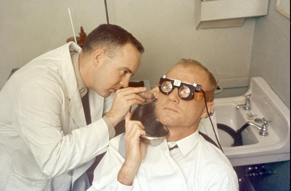 1962: újabb egyensúlyérzék teszt. A kutatóorvos vizet folyat Glenn fülébe, miközben a szemmozgásra gyakorolt hatását méri.