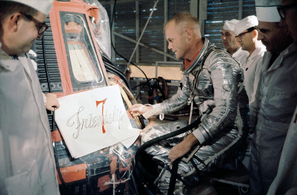 1962. február 20.: Glenn és NASA technikusok az űrhajó nevének felfestése előtt.