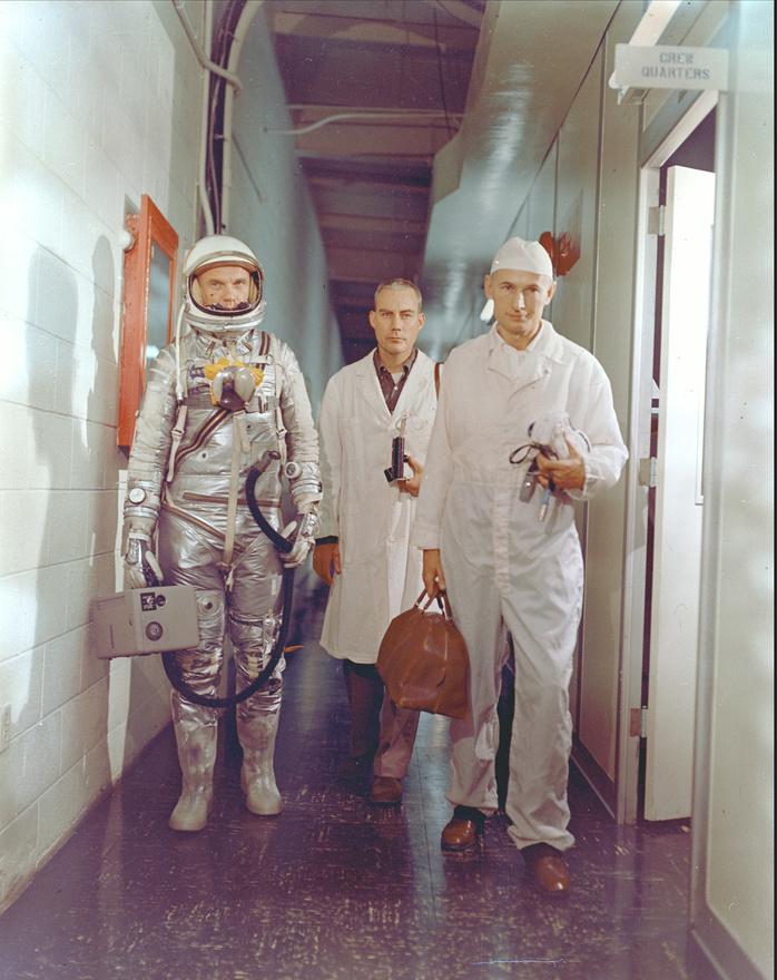 1962. február 20., start előtti pillanat: Glenn a startállás felé halad, kezében az űrruhára csatlakoztatott hordozható szellőztetőgép. Társaságában William Douglas repülőorvos és Joe Schmitt felszerelés-specialista.
