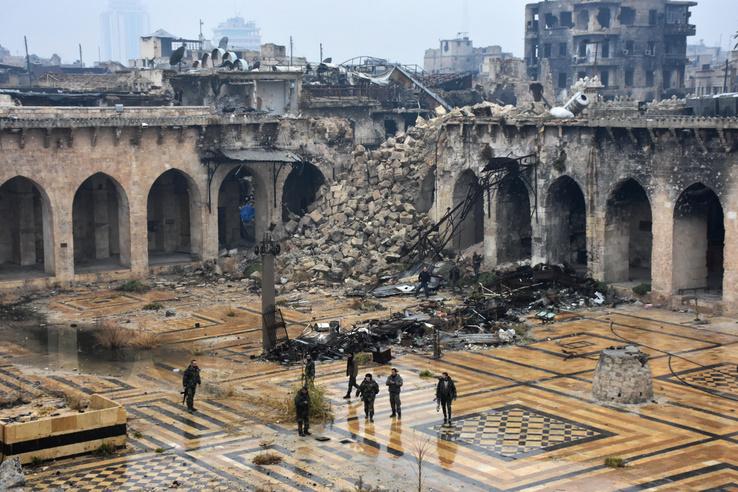 A lebombázott Umayyad mecset épületében sétálnak kormánypárti katonák.