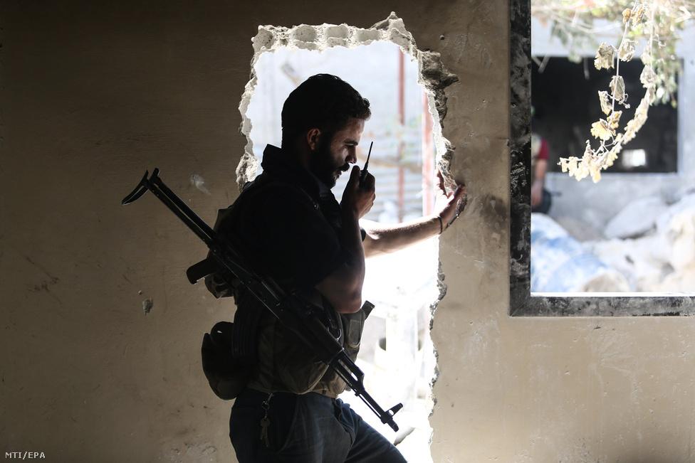 Az ellenzéki Iszlám Hadsereg nevű szervezet egyik katonája rádiózik társaival egy lerombolt épület ajtajában.