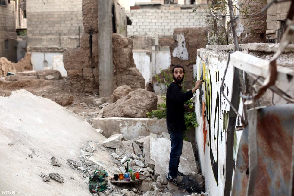Noor szíriai graffitimûvész dolgozik legújabb alkotásán a főváros Damaszkusz Kabun negyedében.