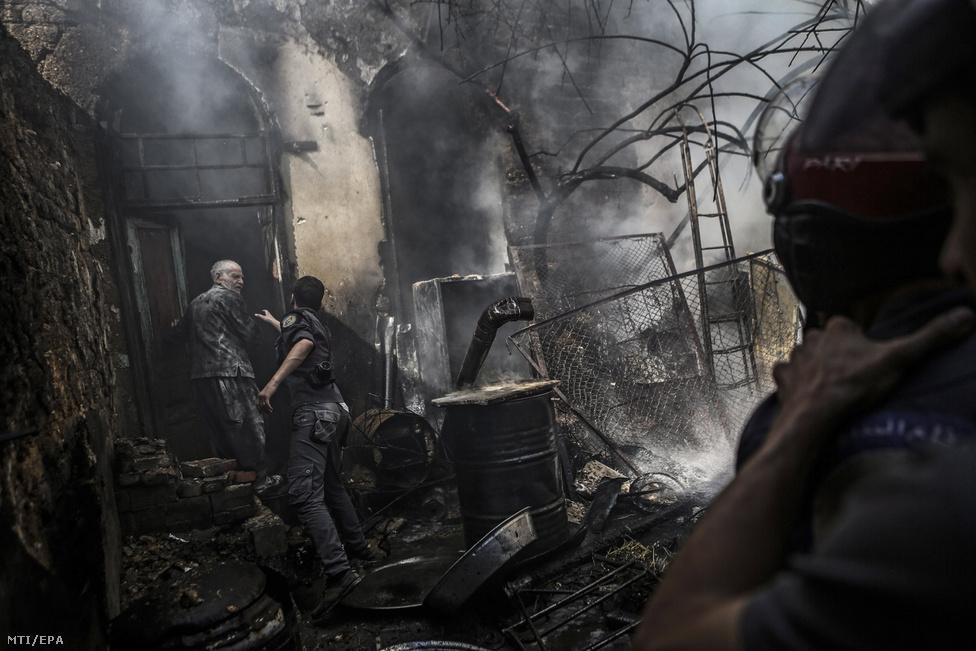 Tűzoltók a füstölgő romok között a város ellen szeptemberben újraindított bombázások után.