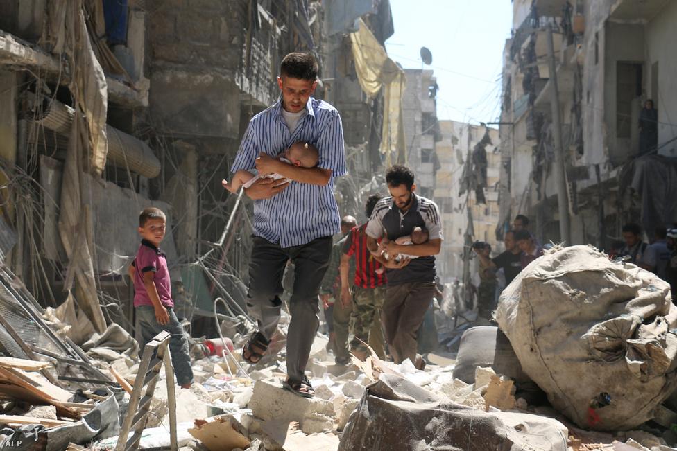 Gyerekeket cipelő szíriai férfiak egy aleppói utcán. A kép szeptemberben készült a város egyik felkelők által ellenőrzött negyedében, egy légicsapás után, amit vagy a szíriai kormány vagy az őket támogató orosz hadsereg indított. A kisbabákat cipelő szíriai férfiakról készült kép az öt éve tartó konfliktus egyik legszívszorítóbb darabja, szeptember óta több száz cikkben jelent meg illusztrációként, nem nehéz belátni, hogy miért.Aleppó a szíriai                          polgárháború előtt 2,5 milliós város volt, Szíria                          legnépesebb települése, a szunnita-arab Damaszkuszhoz                          képest egy soknemzetiségű, sokvallású metropolisz. 2012                         -ben nyomultak be az Aleppó körüli településekről az                          ellenzéki harcosok a város keleti felébe, amire az                          Aszad-rezsim a rendszeressé váló megkülönböztetés                          nélküli bombázással és tüzérségi tűzzel reagált. Az                          évekig tartó harcokba bekapcsolódtak a Hezbollah                          harcosai, az aleppói kurd negyedet szilárdan megszállva                          tartó kurd milícia, az YPG, valamint az al-Kaida szíriai                          fiókszervezetének, az an-Núszra Frontnak a dzsihadistái                          is. 2013-tól északkelet felől megjelentek a felívelőben                          lévő Iszlám Állam dzsihadistái is, akik sorra vették be                          Aleppó keleti elővárosait. A mérhetetlen pusztítással                          járó aleppói helyzetet egy képzeletbeli Budapestre                          átvetítve itt                          értheti meg jobban.                                                  Az erők egyensúlya 2015 végén, az Aszadot támogató orosz                          intervencióval tört meg. A névleg a terroristákat, de                          valójában az Aszad-ellenes erőket célzó légioffenzívának                          