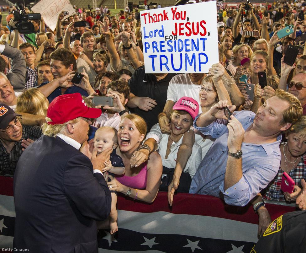 Az egész éves amerikai kampányőrületből ehhez a fotóhoz térek vissza leggyakrabban. Volt egy Nagyképünk, amiben összegyűjtöttük Trump és a legnagyobb rajongóinak intenzív találkozásait, de ez a fotó még abban a válogatásban is kilóg a sorból. Trumpot csak hátulról-profilból és a jellegzetes haja nélkül látjuk, a kép mégis csak róla szól igazán. Hisztéria, vallásos imádat, társadalomrajz - minden egyben ezen a tömegjeleneten. Én a mai napig nem tudtam megfejteni, kihez tartozik az a belógó kar a rózsaszín baseball-sapka mellett.A legtöbben nem sok esélyt adtak volna neki, amikor 2015                          nyarán bejelentette az elnökjelölti indulását, de a                          milliárdos Donald Trump előbb a republikánusok                          jelöltségét söpörte be a pártvezetés                          által támogatott jelöltek orra elől, nyerte meg                          november 8-án az amerikai elnökválasztást a demokrata                          Hillary Clinton ellen, hogy számos republikánus vezető                          politikus nem volt hajlandó mögé állni.                                                   Trump a kampány során egymás után keveredett botrányos                          ügyekbe vitatható húzásai és megszólalásai miatt,                          azonban Clintonnak a külügyminiszterként magán                          emailszerverén folytatott levelezése körüli botrány                          mellett a Clinton Alapítvány körüli ügyekkel is szembe                          kellett néznie. Az utolsó pillanatban is előkerülő                          emailbotrányon kívül azonban leginkább az számított,                          hogy Trump tudta megszólítani  a kiábrándult,                          vidéki fehér amerikai szavazókat. Az elnökválasztási                          kampányt, és az azóta eltelt időszakot, Trump                          kabinetjének kiválasztását Fehér Ház                          blogunkban követtük.