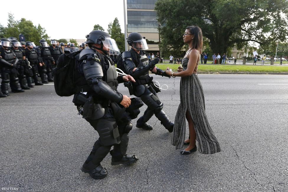 Amerikában az elnökválasztás mellett az év egyik legforróbb témája a rendőri túlkapások voltak.  A rendőrök által viselt kamerákból megismert jelenetek tanulsága, hogy az amerikai járőrök kezében túl könnyen elsül a fegyver az első gyanús vagy félreérthető mozdulatra. A sorozatos esetek után indult utcai tüntetések egyik emblematikus pillanata volt ez a kép, ahol három rendőr lefog és elvezet egy nőt, aki mozdulatlanul demonstrált előttük.Louisiana állam fővárosában, Baton Rouge-ban azután                          kezdődtek nyáron tüntetések, hogy nyilvánosságra került                          egy mobillal készített videó, amin látszott, hogy két                          fehér rendőr lefogott, és lelőtt egy Alton Sterling nevű                          fekete férfit. Az észak-karolinai Charlotte-ban pedig                          azután is zavargás kezdődött, hogy egy fekete rendőr                          lőtt le egy fekete férfit, szükségállapotot is ki                          kellett hirdetni. Sokkal több embert ölnek meg a                          rendőrök Amerikában, mint bárhol máshol a világon, és a                          faji feszültség éppen Amerika első fekete elnöke alatt                          erősödött fel újra, Barack Obama elnökségének utolsó                          évét. A helyzet azonban bonyolultabb, mint elsőre tűnik,                          erről itt írtunk bővebben.