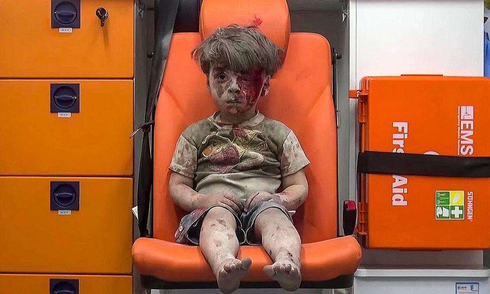 Ez az a fotó, amit nem kéne megmagyarázni, sőt, el sem kellett volna jutni odáig, hogy elkészülhessen.Az                          aleppói harcok szimbolikus jelképe lett az a                          négyéves kisfiú, akit porosan, véres arccal fotóztak le,                          miután kimentették egy lebombázott épület romjai alól.                          Több millióan menekültek el a városból, de még a nyáron                          is legalább 300 ezer ember élt az alig 6-7000 milicista                          által védett ellenzéki negyedekben. A városban hónapok                          óta humanitárius katasztrófahelyzet uralkodik, november                          végére az ostomlottak kevesebb, mint 10 százalékához                          jutott el az élelmiszer-, gyógyszer- és ivóvízsegély. Az                          alacsony intenzitású, de fel-fellángoló állóháború a                          békeidőben csodálatos várost romhalmazzá változtatta;                          történelmi városfalait szétlőtték, legendás piacát tűz                          emésztette el. A pusztításban mindenki részt vett, a                          kormánycsapatok és az orosz légierő elsősorban a                          rendszeres bombázásokkal, az iszlamisták pedig                          történelmi emlékek megsemmisítésével.