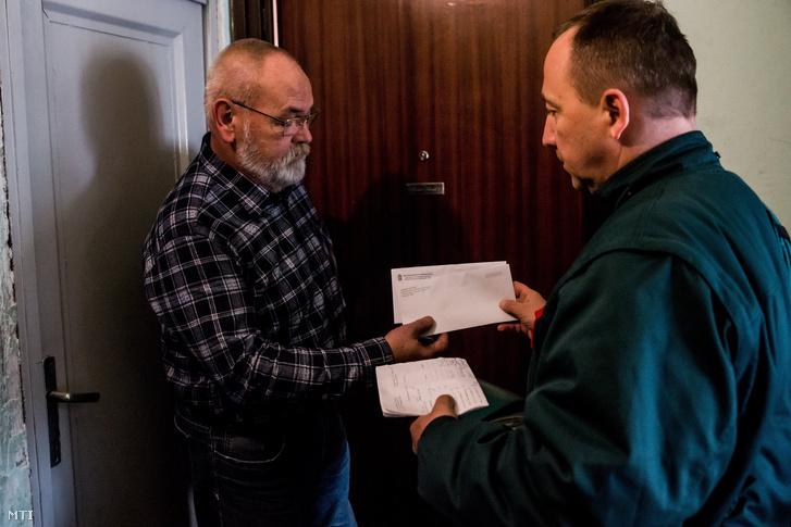 A Magyar Posta Zrt. munkatársa a nyugdíjasoknak szánt Erzsébet-utalványokat tartalmazó borítékot és Orbán Viktor miniszterelnök köszöntõ levelét kézbesíti Budapesten 2016. december 13-án.