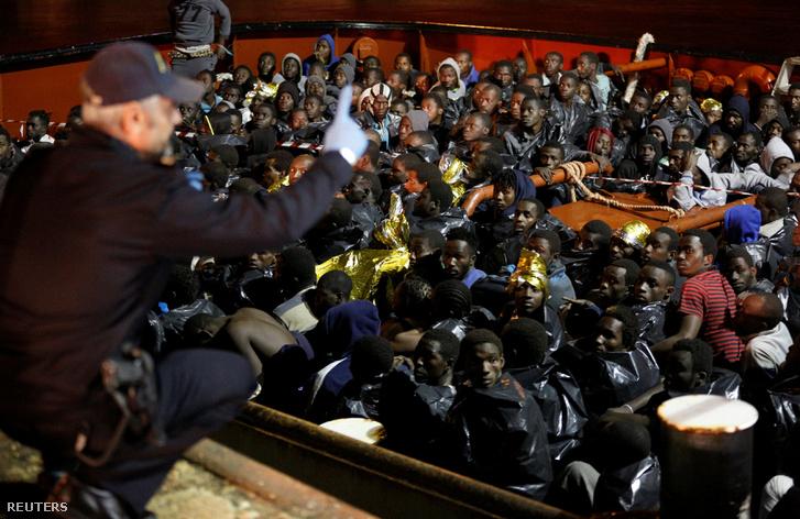 Menekültek várják, hogy elhagyhassák hajójukat a szicílai Augusta kikötőjében, 2016. december 14-én.