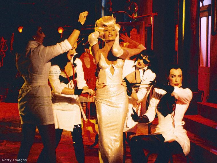 Linda Evangelista a Freedom klipjében teát főz pulóverben, itt egy fehér estélyit mutat be parókában.