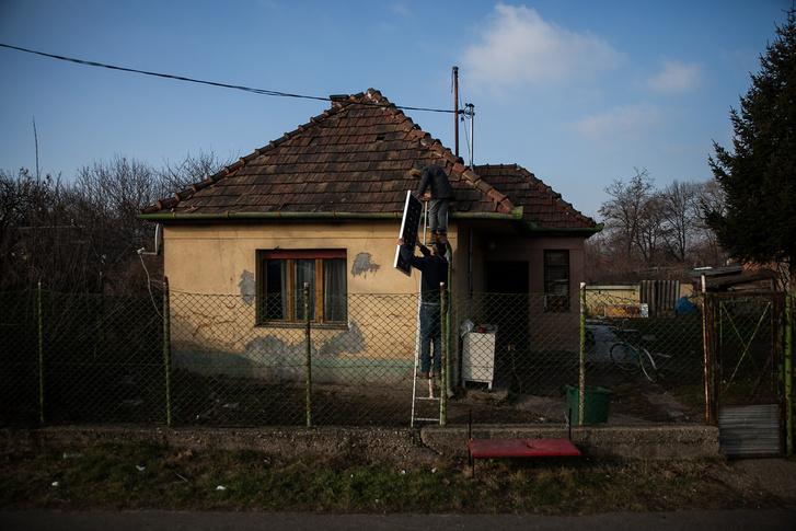 A Romaversitas Alapítvány munkatársai napelemet erősítenek a ház tetejére