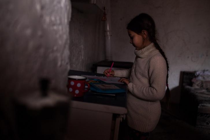 Anna lánya rajzol az ablakból beszűrődő utolsó délutáni fénynél. A palackra rögzített LED-sort az akkumulátorra kötve tudják bekapcsolni.