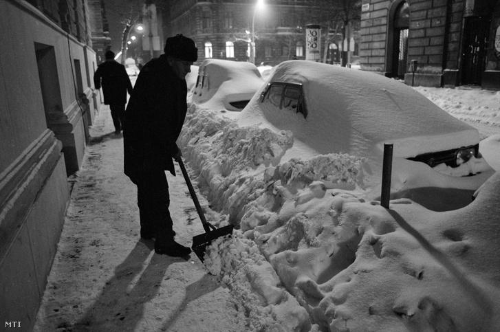 Budapest, 1987. január 14. Egy férfi havat lapátol az utcán hajnalban. Az intenzív havazás miatt az utcán parkoló autókat belepte a hó, a kenyérellátás akadozik.