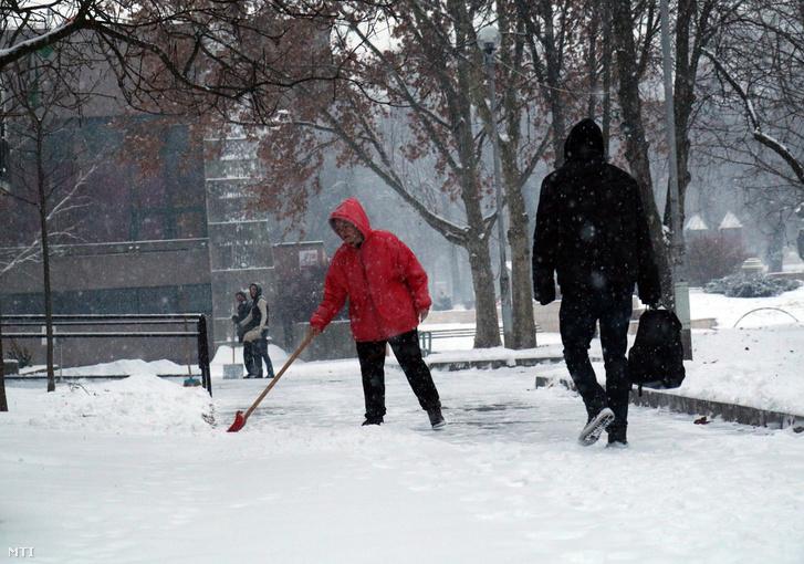 Havat lapátol egy nő az esti havazás után Miskolcon