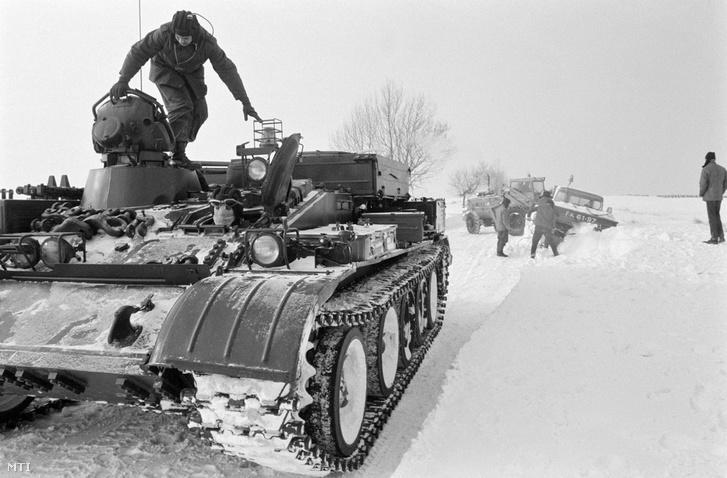 """1987. január 13. Honvédségi jármű segít Borsod megyében a hóban elakadt járművek kiszabadításában. Az előtérben egy VT-55 """"Kisbika"""" csörlős harckocsimentő készül a munkához, a háttérben egy BM Volvo homlokrakodó menti az árokba csúszott munkagépet."""
