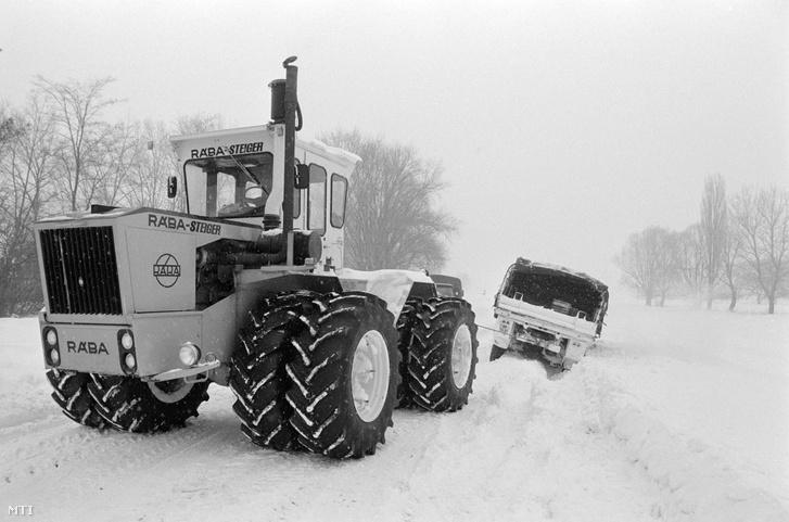 Lébénymiklós, 1987. január 17. Egy Rába-Steiger 250, duplakerekes mezőgazdasági vontató húzza ki az útról lecsúszott mentésre induló honvédségi teherautót, mely a lébénymiklósi termelőszövetkezet szarvasmarha-telepére tartott, ahol a rendkívüli időjárás miatt, a hó súlya alatt beomlott egy épület.