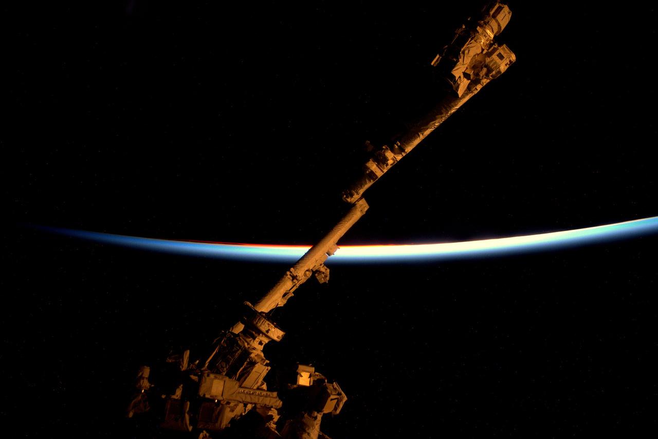 Az űrállomás robotkarja, a Canadarm, a háttérben egy naplemente utolsó pillanata.