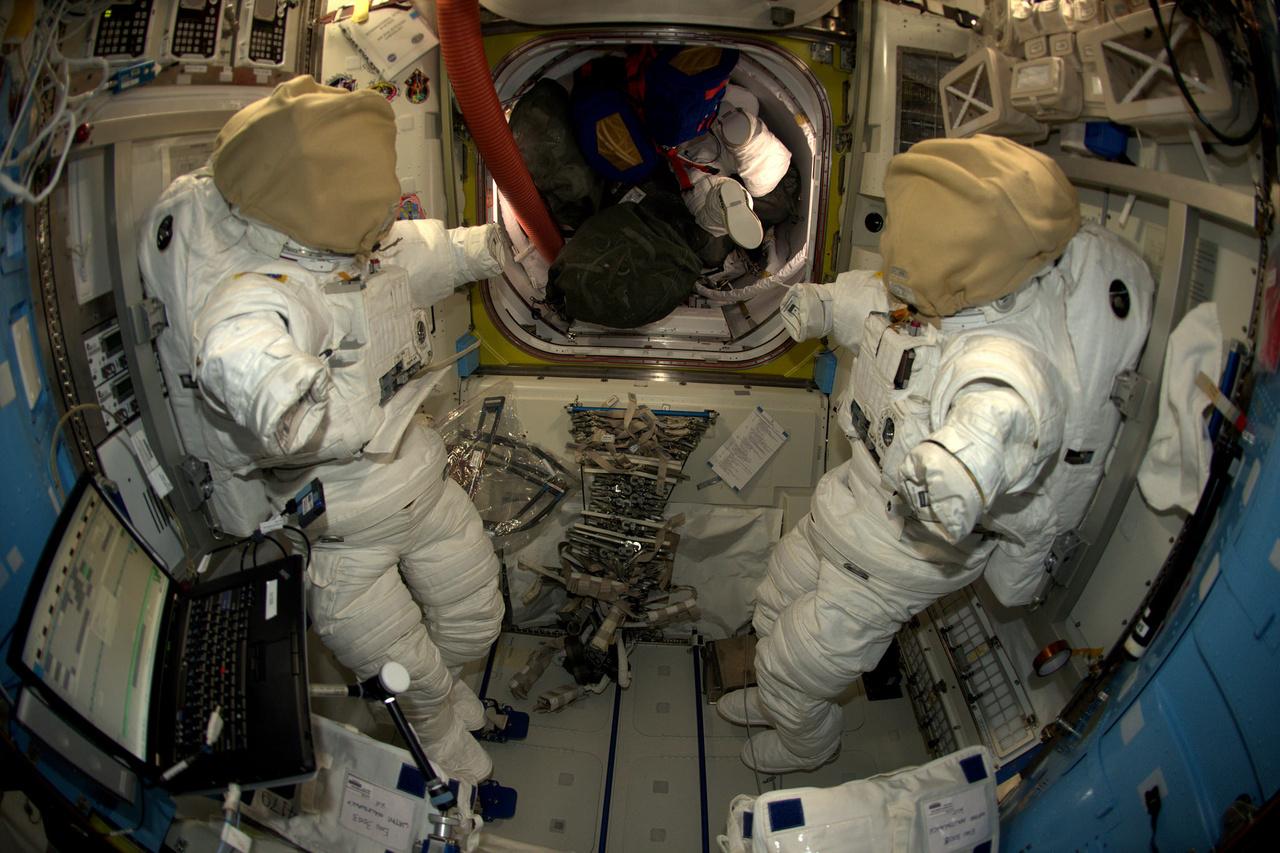 A Nemzetközi Űrállomás légzsilipe, ezen keresztül lépneik ki az űrhajósok, amikor űrsétára mennek. A képen két készenlétben lévő űrruha látható.