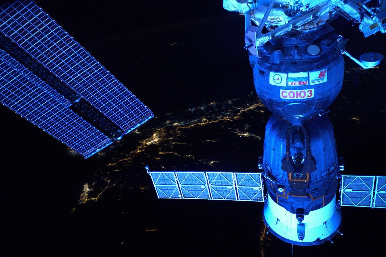 Az űrállomás napelemei és egy, az ISS-hez dokkolt Soyuz űrhajó, a háttérben közel-keleti fények, november 26-án.