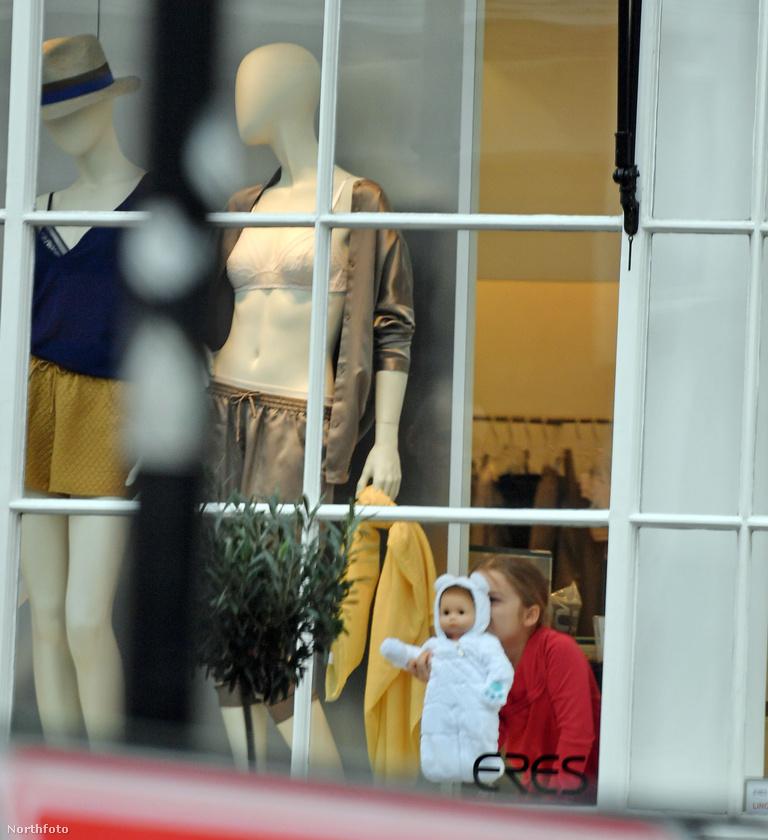 A kis Beckham-lány még az esős időben várakozó testőrükről sem feledkezett meg - így integetett a boltból ő és a baba