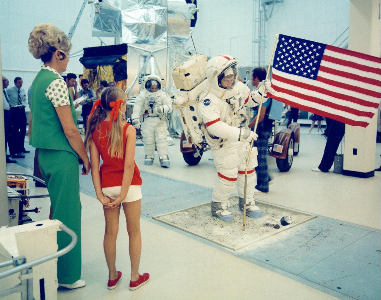 Barbara, Cernan felesége, és lányuk, Teresa azt figyelik, hogyan gyakorolja az űrhajós az amerikai zászló kitűzését.