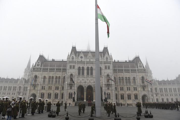 Katonai tiszteletadással felvonják, majd félárbócra eresztik a nemzeti lobogót a veronai buszbaleset áldozataiért elrendelt nemzeti gyásznapon az Országház előtti Kossuth Lajos téren 2017. január 23-án.