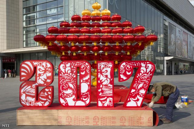 Egy munkás az utolsó simításokat végzi egy bevásárlóközpont elé helyezett újévi dekoráción