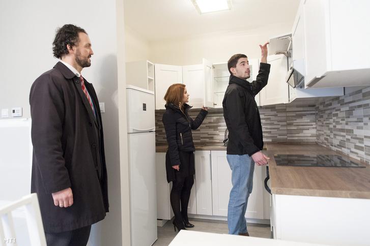 Ingatlanközvetítő iroda munkatársa mutat meg egy új építésű győri lakást egy fiatal párnak