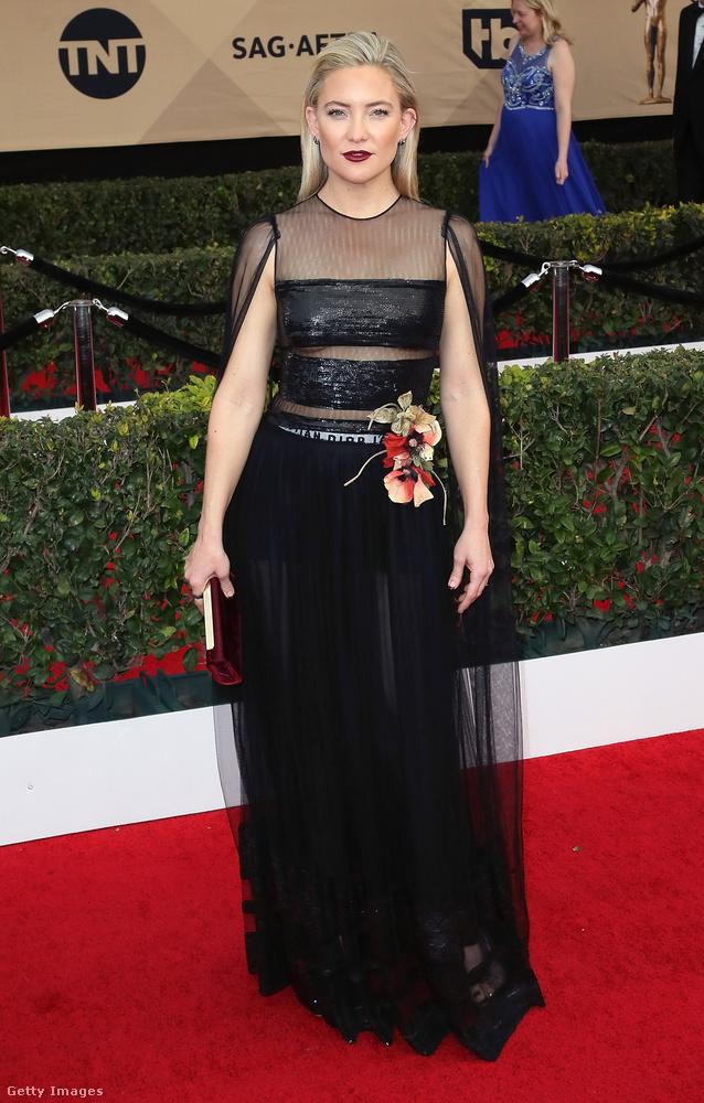 Kate Hudson fogott egy kicsit trendi, kicsit uncsi, kicsit bugyis/átlátszó fekete ruhát (köszönjük, Christian Dior), és egy totál váratlan helyen rárakott egy jó nagy művirágot, aminek semmi köze semmi máshoz
