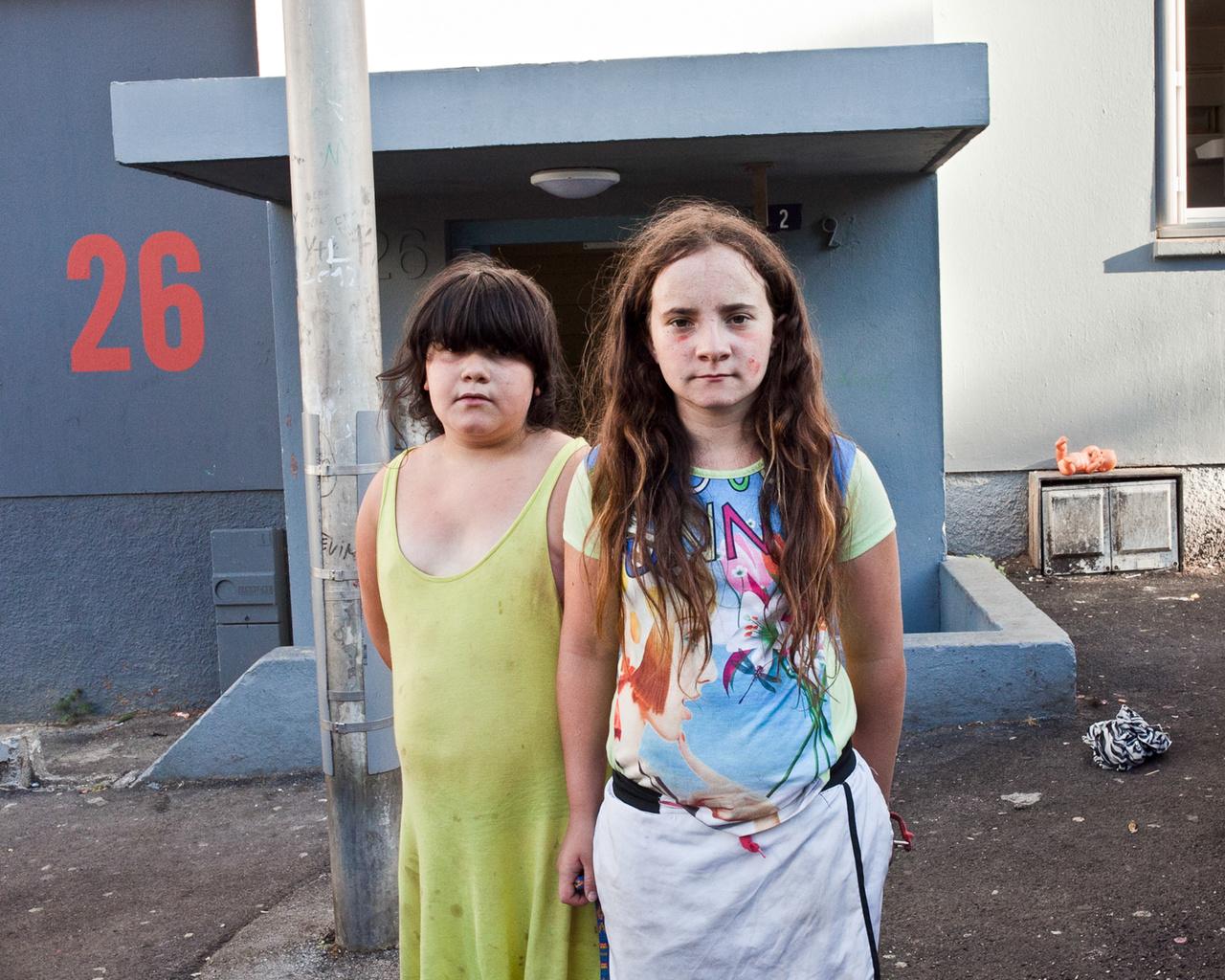 Balra a csodálkozóbb Maddelena, mellette szigorúbb arccal Ilona. A lakótelepek egyik legjellemzőbb vonása, hogy nincs ott semmi. Ilonáék ezt épp a nyári szünetben élhetik át, mert a szüleik nem tudták befizetni őket táborokba vagy bármi más utazásra. Saját tapasztalataim alapján a lakótelepi gyerekek egyébként a mindent elborító sivárságot nem élik meg olyan tragikusan, mint a szüleik vagy a külső szemlélők.  Csak a képen például egy bő órányi játék van,  a kinn hagyott babát például el lehet rugdosni egy darabig, vagy be is lehet tenni a földön lévő csíkos szatyorba és úgy rugdosni.  A trafószekrénynek kinéző holmit pedig szinte muszáj teljesen kinyitni és megvizsgálni, félig már amúgy is nyitva van. Vagy ha szereznek egy csavarhúzót, talán le tudják feszíteni kettes számjegyet az ajtó mellőt, tök felesleges ezerszer kiírni a házszámot, és még jó lehet valamire. Persze a lányok jó eséllyel konszolidáltabbak, Ilona inkább ugrókötelezésből, Maddelena babázásból állhatott be egy gyors fotóra.