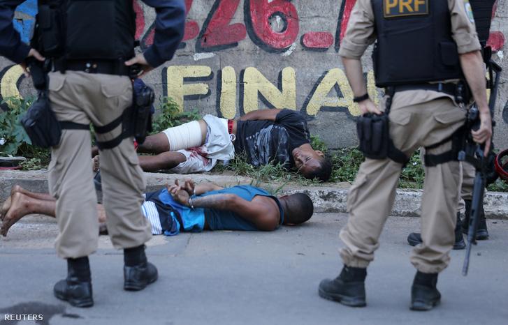 Két motorlopással gyanúsított férfi fekszik a földön, az őket elfogó rendőrök közt