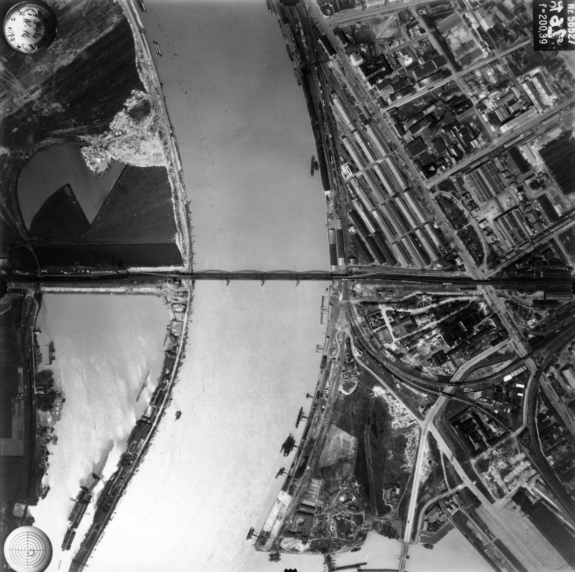 Még nagyobbat változott a Duna-part Délen. A Déli összekötő vasúti híd akkor még a pesti oldal                         ipartelepeit kapcsolta össze a budai oldalon fekvő nagy semmivel. Budán annyira nem volt semmi,                         hogy szinte csak a vasúti töltés emelkedik a parti mocsár fölé. A Lágymányosi-öböl még egészen a                         vasútig tart: a most épülő BudaPart helyén víz van, de az Infopark és az egyetemi negyed helyén is                         egy tó tükre csillog. Túloldalt, ahol most a Müpa és a Nemzeti Színház áll, raktárak sorakoznak                         katonás rendben. Igazi logisztikai központ volt ez vízi és vasúti kapcsolattal, és rengeteg ipari                         létesítménnyel. Az utóbbiakból mára csak a gyönyörű Közvágóhíd és a klassz irodaházzá alakított                         Borjúvásárcsarnok maradt meg.
