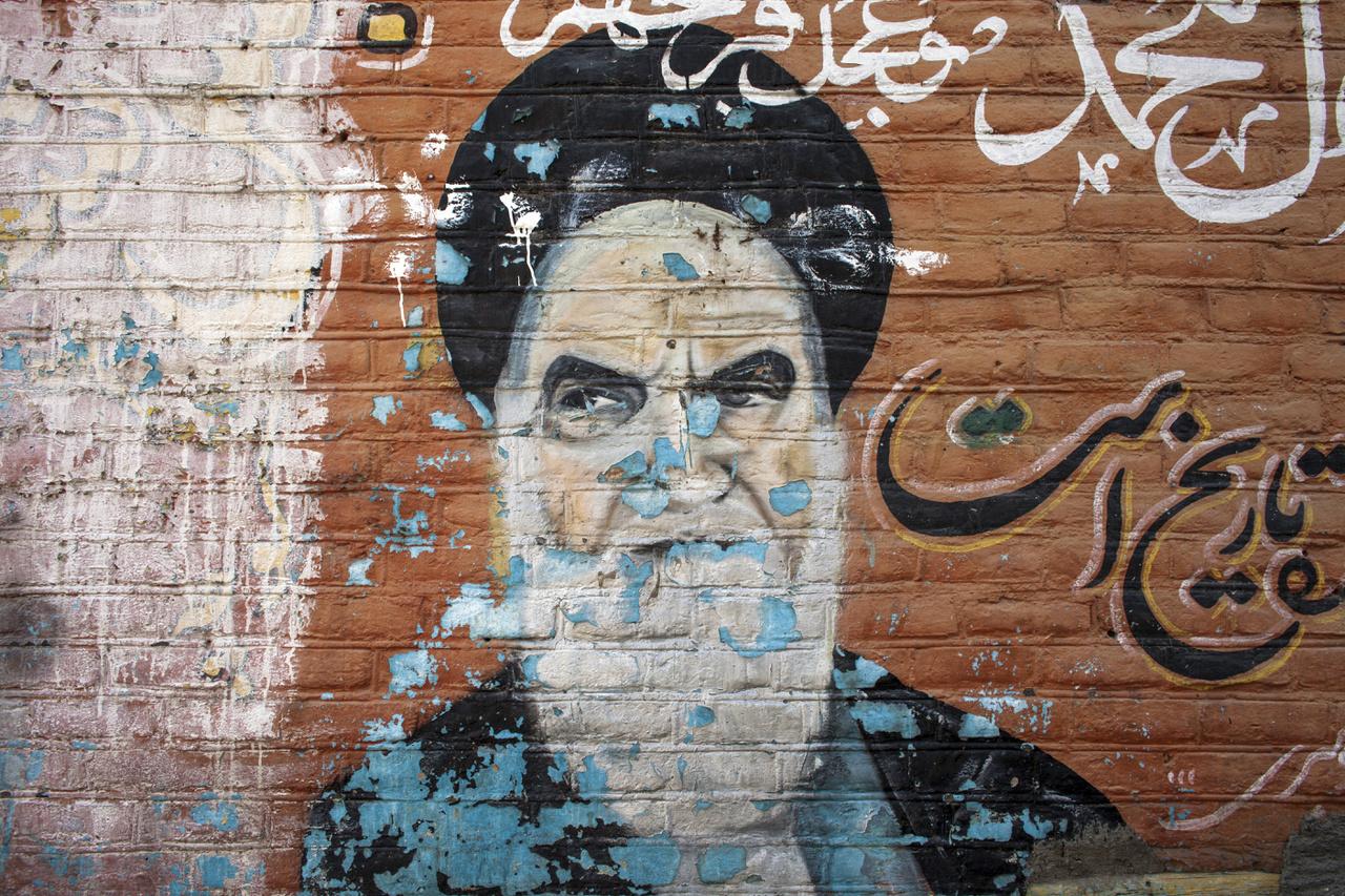 Zavarbaejtően elhanyagolt falfirka Khomeini Ajatollahról, a forradalom atyjáról. A forradalom után haláláig, tíz éven át volt Irán legfelsőbb vezetője, azóta ebben a pozícióban Ali Hamenei van. A legfelsőbb vezető kezében összpontosul a valódi hatalom: ő a hadsereg főparancsnoka, neki felel a titkosszolgálat, háborút hirdethet, ő szabja meg a bel- és külpolitikai irányt, ő nevezi ki az Őrök Tanácsának tagjait. Az államfő ennél alacsonyabb pozíció – ezért is lehet, hogy különböző frakciók valóban megküzdhetnek érte, a legfelsőbb vezető megkérdőjelezhetetlen tekintélyét ez nem érinti. Az elnök súlya Iránban olyan, mint egy kormányfő egy elnöki központú köztársaságban. Persze a hasonlat sántít, elvégre a legfelsőbb vezető nem választáson nyeri el pozícióját: formálisan a szakértők tanácsa jelöli ki. A szakértők tanácsát viszont a legfelsőbb vezető által kiválasztott Őrök Tanácsa jelöli ki, így a testület nem megy szembe Hameneivel. A kérdés inkább az, hogy a 78 éves vezető halála után hogyan zajlik le az utódlás