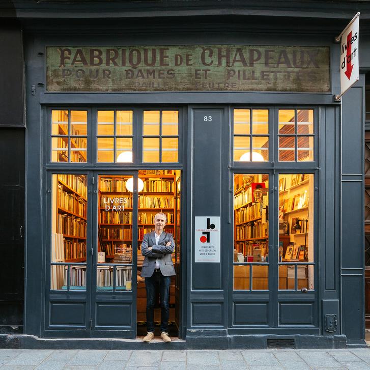 Stefan Perrier áll boltja előtt, ami a felírat szerint kalapüzlet, valójában könyvesbolt